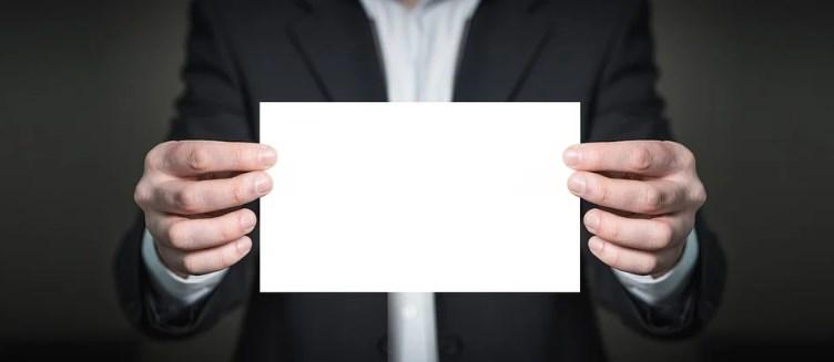 Мужчина в деловом костюме держит в руках лист бумаги