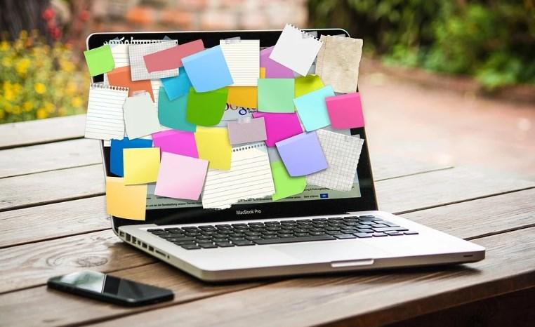 В саду на деревянном столе лежит смартфон и стоит ноутбук, на который наклеены разноцветные стикеры